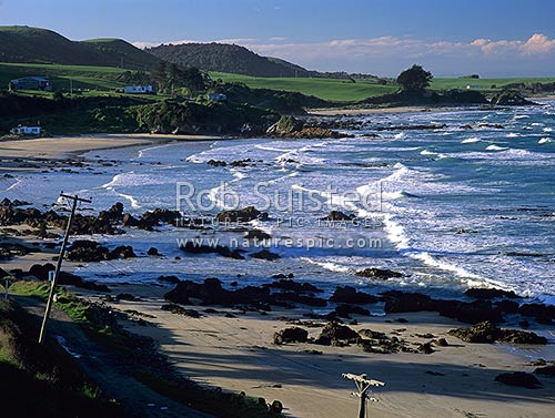 Tirohanga beach and houses, near Nugget Point, Catlins, Clutha District, Otago Region, New Zealand (NZ) stock photo.