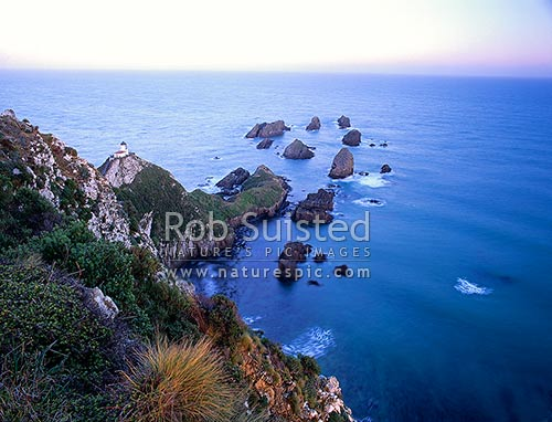 The Nuggets - Nugget Point and lighthouse at dusk, Catlins, Clutha District, Otago Region, New Zealand (NZ) stock photo.
