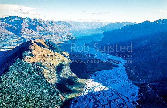 Looking down the braided lower Dart River over Mount (Mt) Alfred (1386m) to Lake Wakatipu, Glenorchy, Queenstown Lakes District, Otago Region, New Zealand (NZ) stock photo.