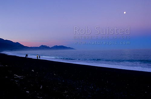 People on Kaikoura beach at sunset/moonrise. Seaward Kaikoura Mountains behind, Kaikoura, Kaikoura District, Canterbury Region, New Zealand (NZ) stock photo.