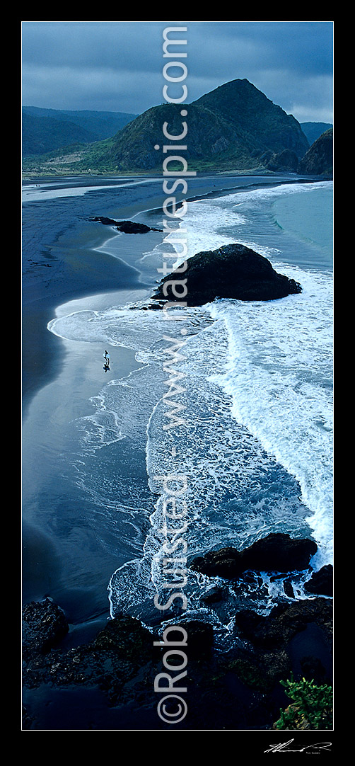 Image of Surf rolling onto Whatipu Beach (black ironsand) at the entrance to Manukau harbour. Surfer leaving the sea, Auckland, Waitakere City District, Auckland Region, New Zealand (NZ) stock photo image