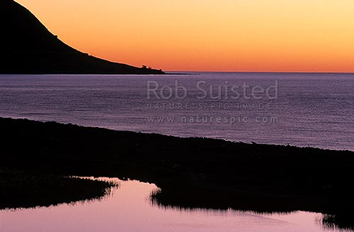 Sunset over Papatea Bay in the Bay of Plenty. Skies and headland reflected in water, East Cape, Opotiki District, Bay of Plenty Region, New Zealand (NZ) stock photo.