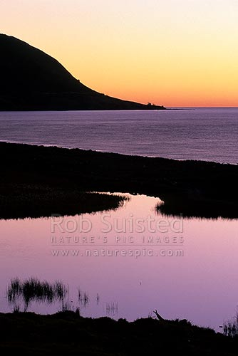 Sunset over Papatea Bay in the Bay of Plenty. Colours reflected in water, East Cape, Opotiki District, Bay of Plenty Region, New Zealand (NZ) stock photo.