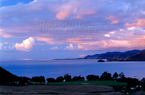 Looking across Omaio Bay to Te Kaha at dusk. Clouds and sea with sunset colouring, Te Kaha, East Cape, Opotiki District, Bay of Plenty Region, New Zealand (NZ) stock photo.