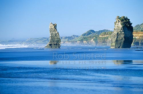 Looking north from Tongaporutu ocean beach at low tide, past the '3 Sisters rocks', North Taranaki, New Plymouth District, Taranaki Region, New Zealand (NZ) stock photo.
