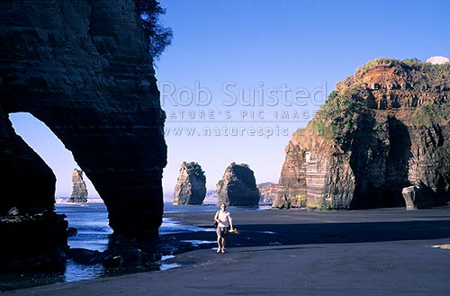 Visitor to Tongaporutu coastline with the '3 sisters rocks' behind, North Taranaki, New Plymouth District, Taranaki Region, New Zealand (NZ) stock photo.
