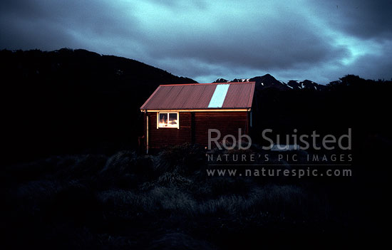 Old Sunrise hut illuminated by early morning sun, Ruahine Forest Park, Central Hawke's Bay District, Hawke's Bay Region, New Zealand (NZ) stock photo.