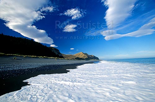 Dramatic cloud formations over a secluded beach on the Kaikoura Coast. Sea foam in foreground, Kaikoura, Kaikoura District, Canterbury Region, New Zealand (NZ) stock photo.