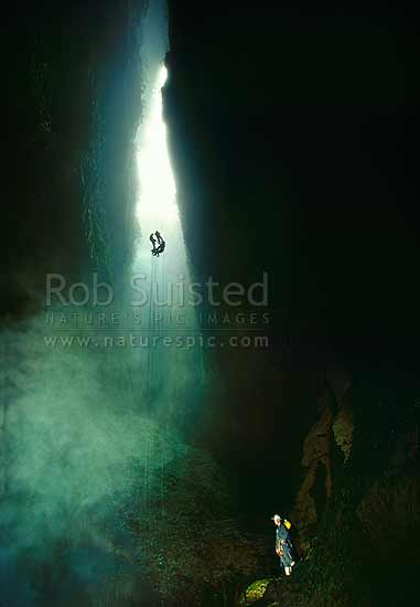 A tour group descending into the misty 'Lost World' cave - 100m abseil and cave tour, Waitomo, Waitomo District, Waikato Region, New Zealand (NZ) stock photo.