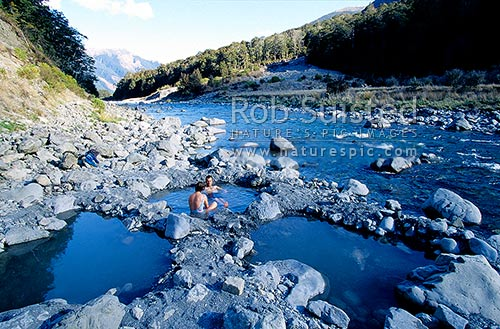 Natural hot pools at Sylvia Flat, Lewis Pass. Couple relaxing in warm pool, Lewis Pass, Hurunui District, Canterbury Region, New Zealand (NZ) stock photo.