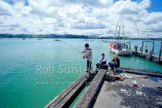 Boys fishing on wharf at Mangonui - Mangonui Harbour in Doubtless Bay, Far north, Northland, Far North District, Northland Region, New Zealand (NZ) stock photo.