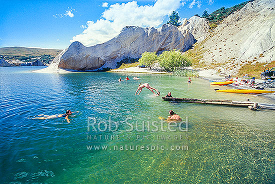 Summer swimming in Blue Lake at Saint Bathans. Lake formed from old gold sluicing operations late 1800, St Bathans, Central Otago District, Otago Region, New Zealand (NZ) stock photo.
