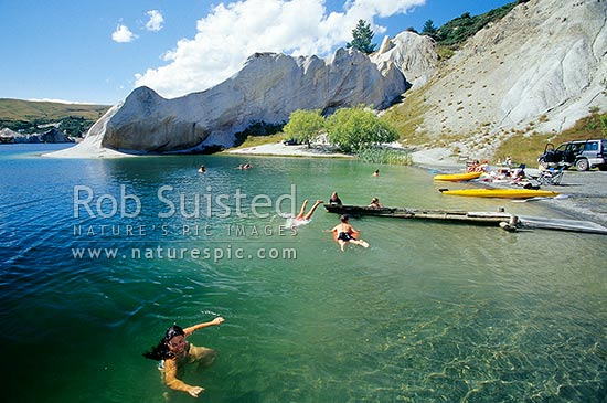 Summer swimming in Blue Lake, Saint Bathans. Lake formed from old gold sluicing operations late 1800, St Bathans, Central Otago District, Otago Region, New Zealand (NZ) stock photo.