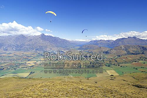 Parapenters above the Kawarau Valley near Queenstown and Lake Wakatipu from Coronet Peak., Queenstown, Queenstown Lakes District, Otago Region, New Zealand (NZ) stock photo.