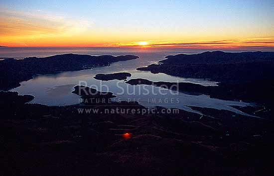 Looking over Lyttelton Harbour at sunrise. Quail Island centre left. Lyttelton at left. Godley Head centre upper left, Banks Peninsula, Christchurch City District, Canterbury Region, New Zealand (NZ) stock photo.