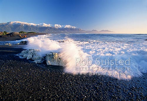 Surf on Kaikoura Beach and snow covered Seaward Kaikoura Mountains, Kaikoura, Kaikoura District, Canterbury Region, New Zealand (NZ) stock photo.