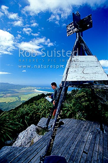 Tramper on the top of Mount (Mt) Hobson (621m) and Trig station. Okiwi and Whangapoua beyond, Great Barrier Island, Auckland City District, Auckland Region, New Zealand (NZ) stock photo.
