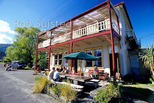 Tourists and travelers drinking at the historic 'Formerly the Blackball Hilton' hotel, Blackball, Grey District, West Coast Region, New Zealand (NZ) stock photo.
