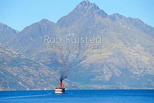TSS Earnslaw - historic steamship on Lake Wakatipu, dwarfed by Walter Peak (1800masl), Queenstown, Queenstown Lakes District, Otago Region, New Zealand (NZ) stock photo.