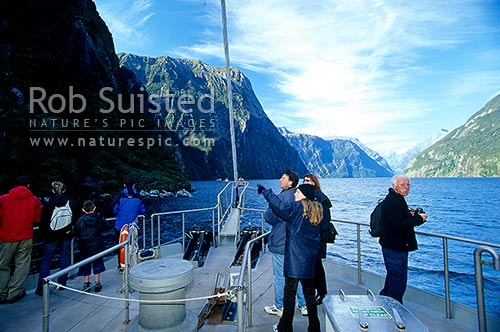 Visitors and people on tourist boat taking a trip up Milford Sound fiord, Fiordland National Park, Southland District, Southland Region, New Zealand (NZ) stock photo.