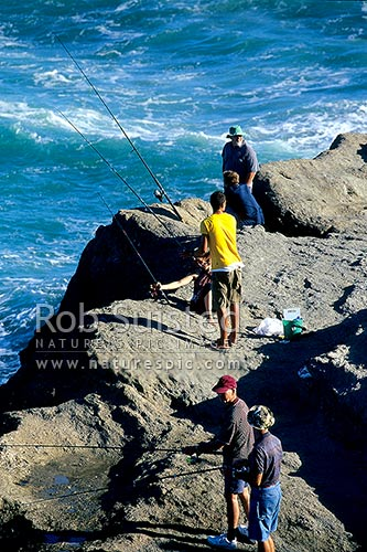 People fishing off the cliffs at Castlepoint. Castle Rock and lagoon behind, Castlepoint, Masterton District, Wellington Region, New Zealand (NZ) stock photo.