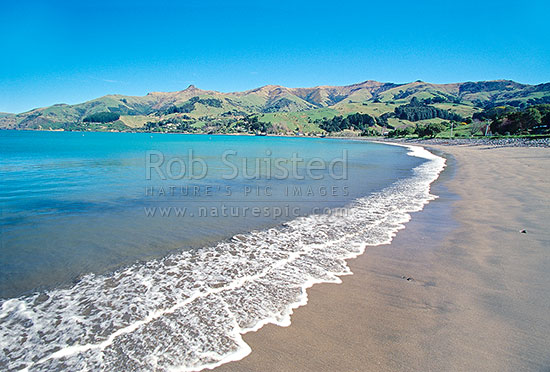 Gentle waves on Wainui Bay beach in Akaroa harbour, Akaroa, Banks Peninsula District, Canterbury Region, New Zealand (NZ).
