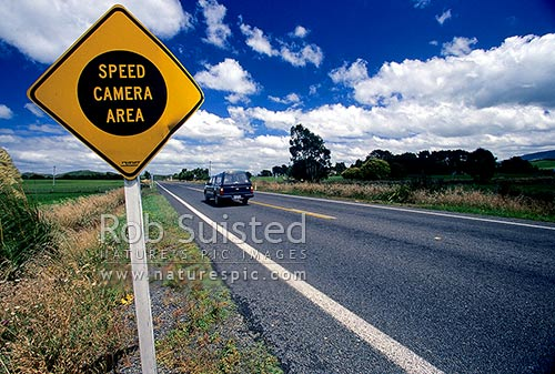 Speed camera sign on State Highway 2 road in the Central Hawkes Bay running through farmland, Dannevirke, Tararua District, Manawatu-Wanganui Region, New Zealand (NZ) stock photo.