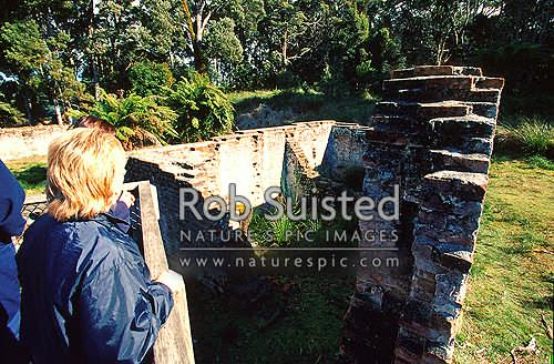 People visitors to historic penal colony remains on Sarah Island. Cell blocks, Strahan, Tasmania District, Australia stock photo.