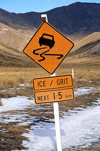 Road sign warning of ice and grit - winter snow, Lindis Pass. State highway 8, Lindis Pass, Central Otago District, Otago Region, New Zealand (NZ) stock photo.