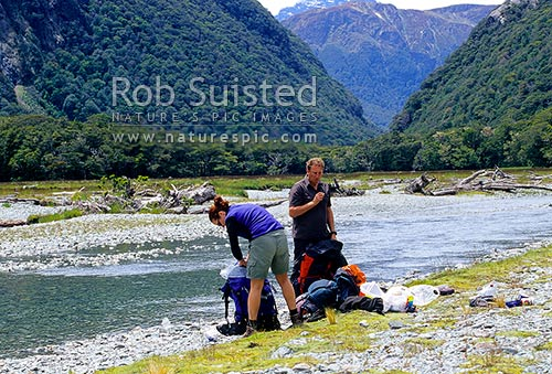 Couple of trampers / walkers taking a break beside the Route Burn, Routeburn Track Great Walk, Mount Aspiring National Park, Queenstown Lakes District, Otago Region, New Zealand (NZ) stock photo.