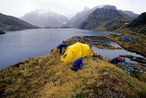 Trampers at alpine tent camp near mountain tarn and lake - Serpentine Mountains, Mount Aspiring National Park, Queenstown Lakes District, Otago Region, New Zealand (NZ) stock photo.