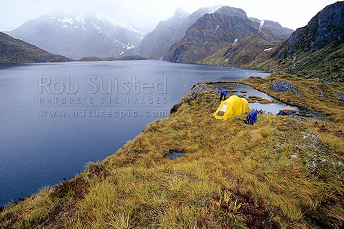 Alpine tent camp near mountain tarn and lake - Serpentine Mountains., Mount Aspiring National Park, Queenstown Lakes District, Otago Region, New Zealand (NZ) stock photo.