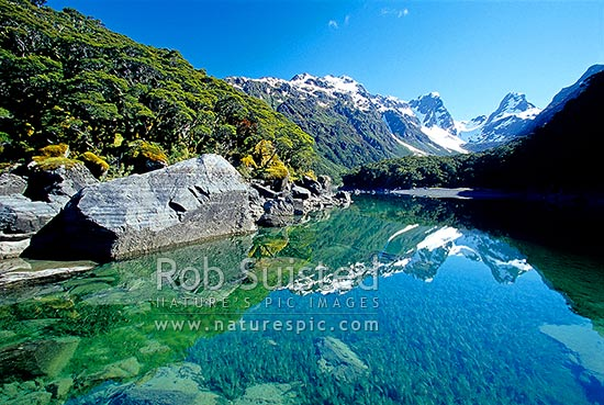 Emily Pass and Emily Peak reflected in calm Lake MacKenzie, Routeburn Track Great Walk, Fiordland National Park, Southland District, Southland Region, New Zealand (NZ) stock photo.