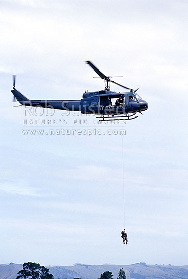Royal New Zealand Air force Iroquois helicopter winching crew member, New Zealand (NZ) stock photo.