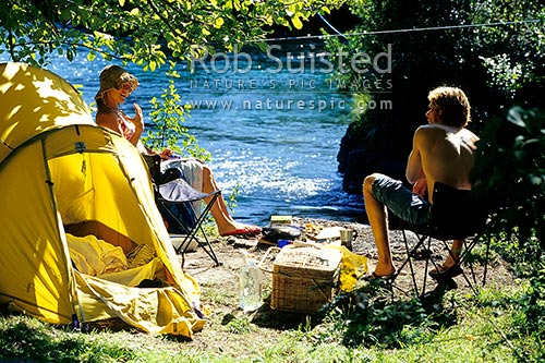 People summer tent camping and picnicking on the banks of the Waikato River near Taupo. Backpacking, Taupo, Taupo District, Waikato Region, New Zealand (NZ) stock photo.