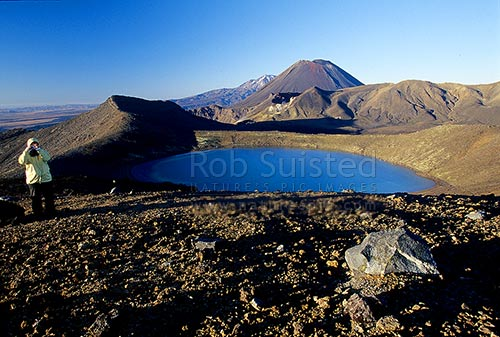 Person above Blue Lake and Red Crater of Mount Tongariro, Mount (Mt) Ngauruhoe (2287m) and Mount (Mt) Ruapehu (obscured) behind. Tongariro crossing tramping track, Tongariro National Park, Taupo District, Waikato Region, New Zealand (NZ).