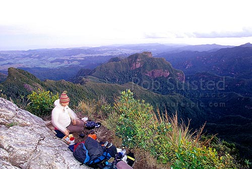 Tramper preparing dinner on the summit of The Pinnacles (788m), above Pinnacles Hut. Coromandel Ranges. Kauaeranga Kauri Trail track, Kauaeranga Valley, Thames-Coromandel District, Waikato Region, New Zealand (NZ) stock photo.