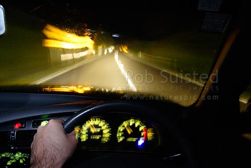 Night driving in fog and rain. Blurred motion and streaked reflections and light. Road hazards. Driving hazard, New Zealand (NZ) stock photo.