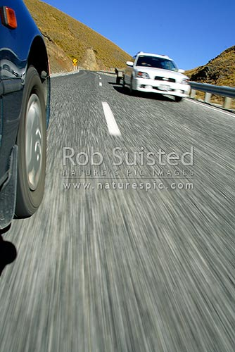 Car driving over Crown Range Road (State highway 89), with oncoming traffic, Cardrona, Queenstown Lakes District, Otago Region, New Zealand (NZ) stock photo.