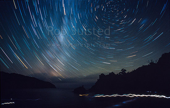 Star trails showing stars revolving around the south pole. Time exposure at night also showing torch trails on beach. Approx 1 hour exposure, Stewart Island, Stewart Island District, Southland Region, New Zealand (NZ) stock photo.