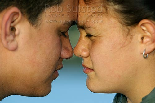 Two Maori teenagers greeting each other with the traditional Maori welcome, a hongi, the pressing together of noses. Happy, smiles, New Zealand (NZ) stock photo.