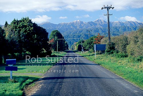 Country Road (Kimberley Rd) heading towards the snow dusted Tararua main range beyond. Tararua Forest Park, Levin, Horowhenua District, Manawatu-Wanganui Region, New Zealand (NZ) stock photo.