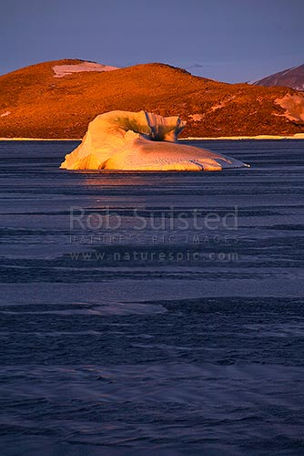 Green iceberg in front of Inexpressible Island, Terra Nova Bay, Ross Sea, at sunset. Note frazzle / frazil / frazil and grease ice on sea surface, Ross Sea, Antarctica District, Antarctica Region, Antarctica stock photo.