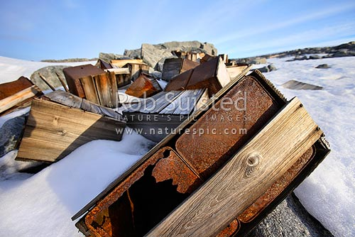 Artefact scatter of store crates behind the Historic 1912-14 Mawson's hut, Cape Denison -'Home of the Blizzard', Commonwealth Bay, George V Land, Antarctica Region, Antarctica stock photo.