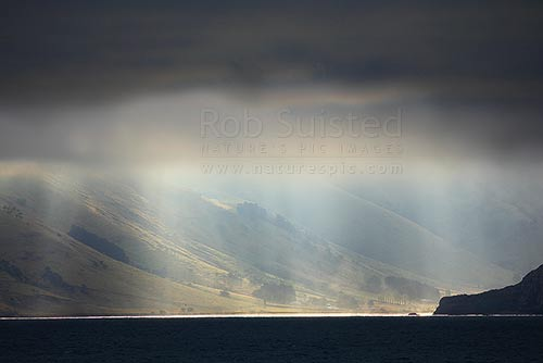 Banks Peninsula coastline with dramatic sun shining under coastal cloud, Banks Peninsula, Christchurch City District, Canterbury Region, New Zealand (NZ) stock photo.