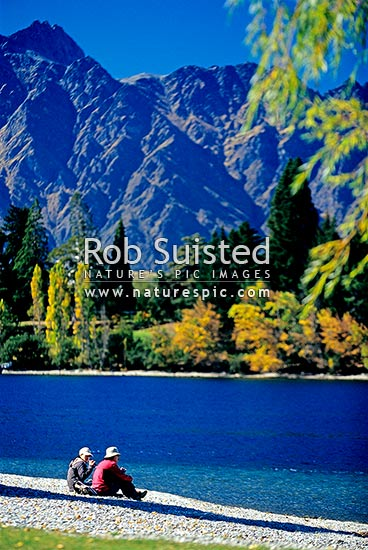 Two tourists sitting on the shore of Lake Wakatipu in Queenstown with The Remarkables Range behind. Autumn colours, Queenstown, Queenstown Lakes District, Otago Region, New Zealand (NZ) stock photo.