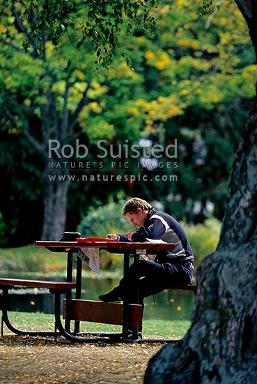 Tourist traveller studying maps and writing letters on park picnic table. Independent traveller, Queenstown, New Zealand (NZ) stock photo.