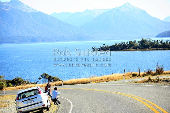 Independent travellers photographing beside Lake Te Anau. Hire car tourists, Fiordland National Park, Southland District, Southland Region, New Zealand (NZ) stock photo.