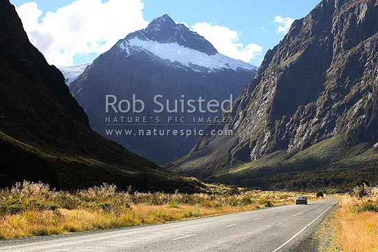 Rental car on road to Milford Sound, Cleddau River Valley. Mt Talbot (2105m) behind. State Highway 94. Winter version available: 38234ts00 to 38237ts00, Fiordland National Park, Southland District, Southland Region, New Zealand (NZ) stock photo.