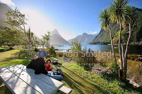 Independent travellers enjoying the sun at Milford Sound, Fiordland National Park. Mitre Peak beyond. Backpackers, Milford Sound, Fiordland National Park, Southland District, Southland Region, New Zealand (NZ) stock photo.